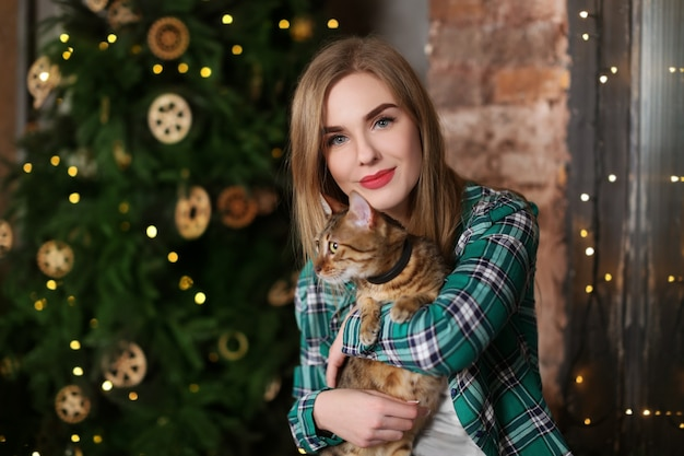 Hermosa mujer joven con lindo gato cerca del árbol de navidad en casa