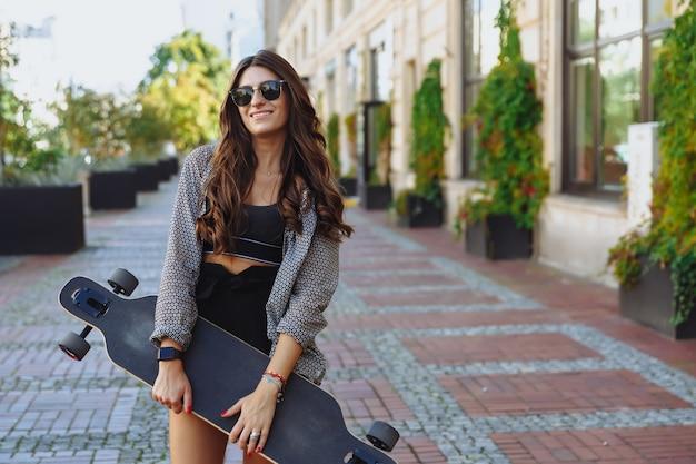 Hermosa mujer joven con longboard en la calle de la ciudad en tiempo soleado.