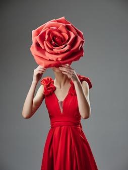 Hermosa mujer joven en un lujoso vestido con rosas, pétalos de rosa, imagen elegante, lápiz labial rojo