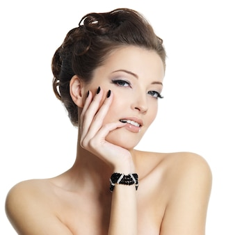 Hermosa mujer joven con manicura negra y peinado elegante posando en blanco