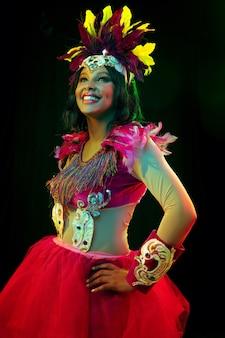 Hermosa mujer joven en máscara de carnaval y elegante disfraz de mascarada con plumas en luces de colores y resplandor en la pared negra