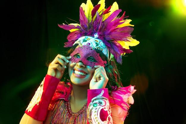 Hermosa mujer joven en máscara de carnaval y elegante traje de mascarada con plumas en luces de colores y resplandor sobre fondo negro