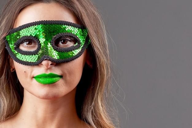 Hermosa mujer joven con máscara de color