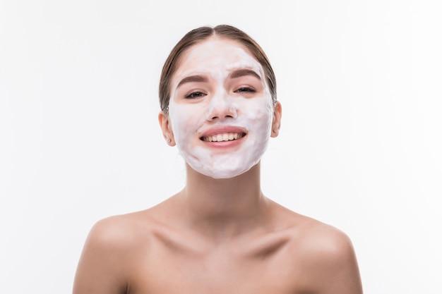 Hermosa mujer joven con máscara facial en pared blanca