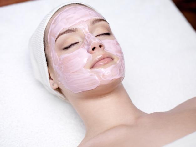Hermosa mujer joven con máscara facial rosa en el salón de spa - en el interior
