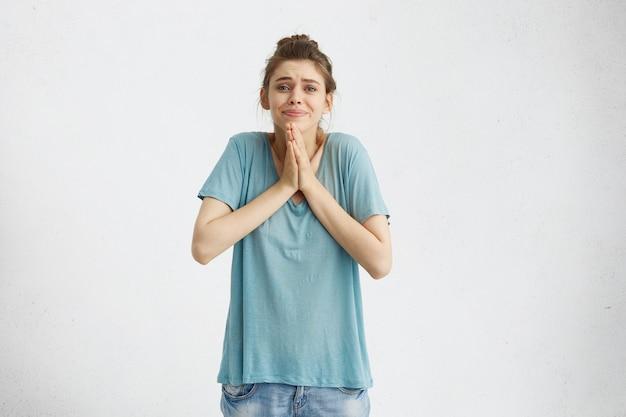 Hermosa mujer joven con mirada implorante y atractiva sosteniendo las palmas juntas frente a ella, pidiendo perdón, sintiendo pena