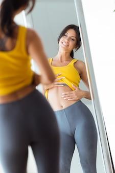 Hermosa mujer joven mirando a sí misma reflexión en espejo en casa.