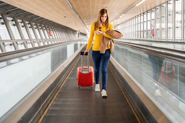 Hermosa mujer joven mirando su reloj en el aeropuerto o estación con su equipaje