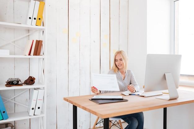 Hermosa mujer joven de negocios trabajando con papeles y computadora en la oficina