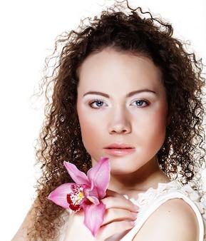 Hermosa mujer joven con orquídea rosa