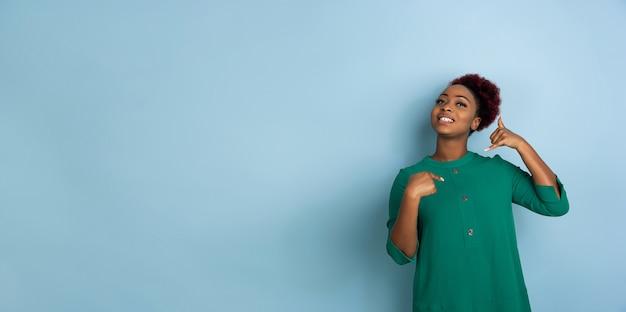 Hermosa mujer joven en la pared azul