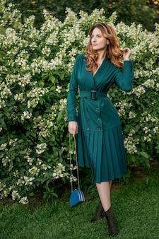 Hermosa mujer joven en un paseo en un vestido verde.
