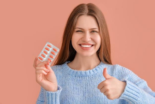 Hermosa mujer joven con pastillas que muestran el gesto del pulgar hacia arriba en la superficie de color