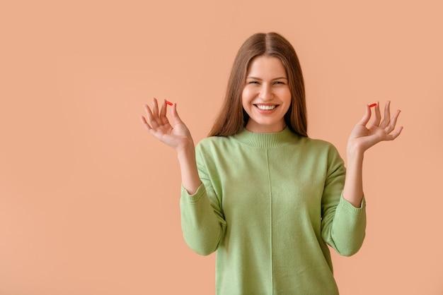 Hermosa mujer joven con pastillas en la superficie de color
