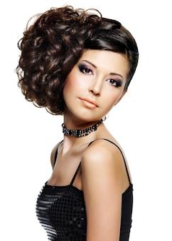 Hermosa mujer joven con peinado de moda y maquillaje glamour - en espacio en blanco