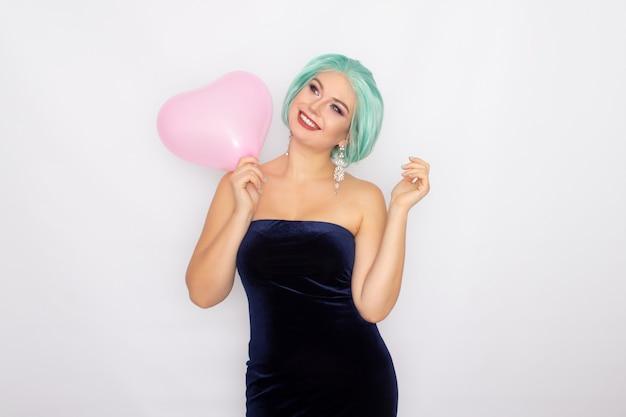 Hermosa mujer joven con pelo corto de menta de pie sosteniendo el globo del corazón