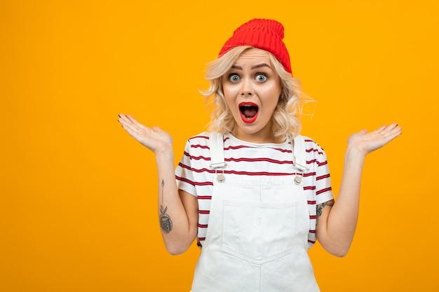 Hermosa mujer joven con el pelo corto y rizado rubio y maquillaje brillante en overol blanco y sombrero rojo gesticulado y sonrisas, retrato aislado en naranja