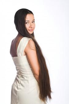 Hermosa mujer joven con pelo largo en blanco
