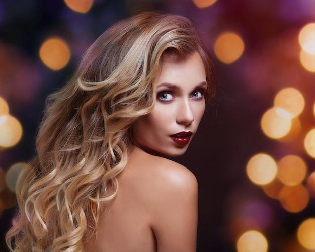 Hermosa mujer joven con pelo largo y joyas.