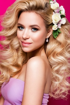 Hermosa mujer joven con el pelo largo, posando en la pared de color rosa brillante