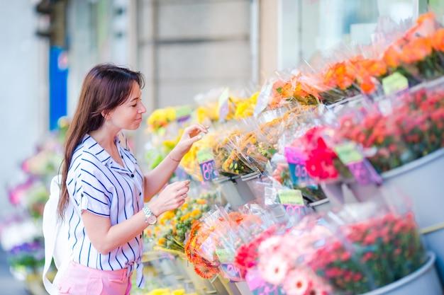 Hermosa mujer joven con el pelo largo seleccionando flores frescas en el mercado europeo