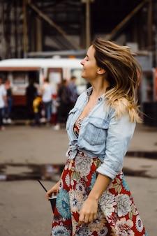 Una hermosa mujer joven con el pelo largo con un vaso de café está sonriendo y riendo.
