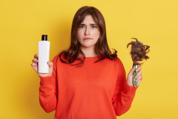 Hermosa mujer joven de pelo oscuro con cabello dañado, mirando y muerde el labio. señora de pie con champú y cepillo en las manos, tiene mucho cabello perdido, necesita tratamiento para un cabello sano.