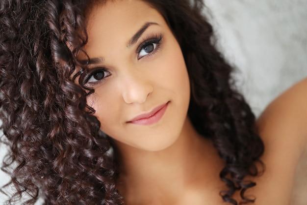 Hermosa mujer joven con pelo rizado negro