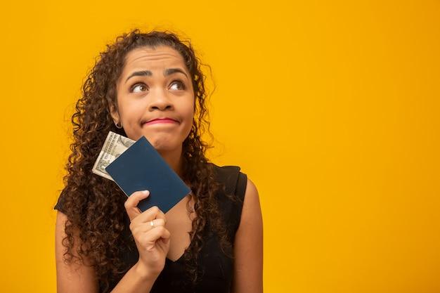 Hermosa mujer joven con el pelo rizado con un pasaporte y dinero, pensando en su próximo viaje.