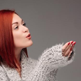 Hermosa mujer joven con pelo rojo y uñas rojas sosteniendo sus manos juntas y soplando en la bola blanca de aligeramiento.