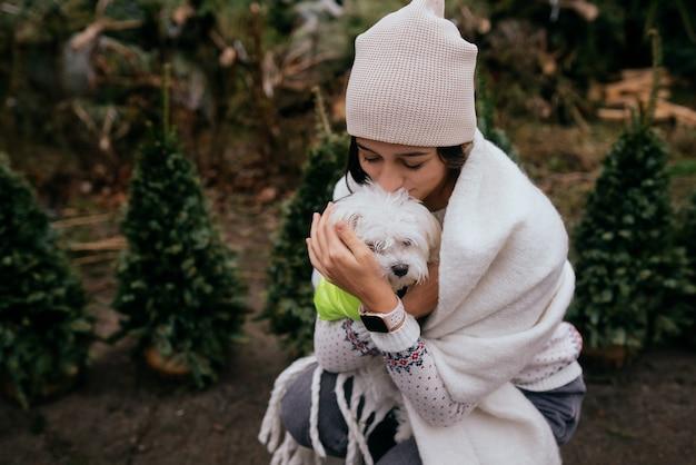 Hermosa mujer joven con un perro blanco