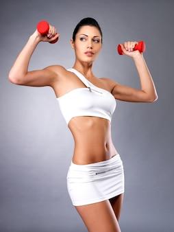 Hermosa mujer joven con pesas - espacio de estudio gris. concepto de estilo de vida saludable.