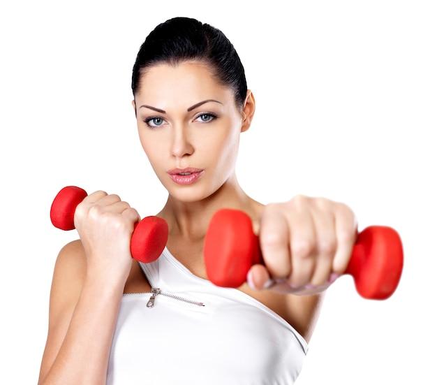 Hermosa mujer joven con pesas - fondo de estudio gris. concepto de estilo de vida saludable.