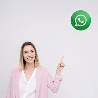 Hermosa mujer joven de pie contra el fondo blanco apuntando al icono de whatsup