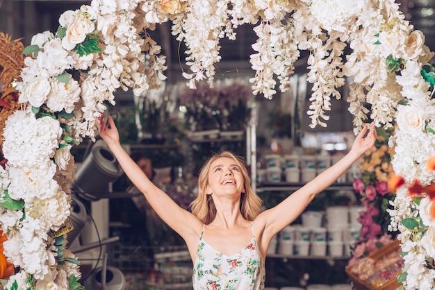 Hermosa mujer joven de pie bajo la entrada curva decorada levantando los brazos y mirando hacia arriba