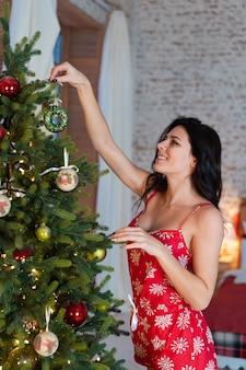Hermosa mujer joven de pie junto al árbol