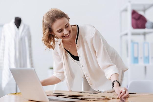 Hermosa mujer joven de pie en un taller y midiendo los patrones de vestimenta con una cinta mientras los mira con una sonrisa feliz