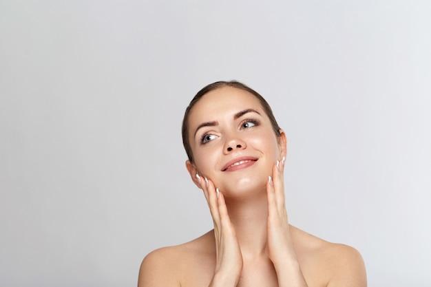Hermosa mujer joven con la piel limpia y fresca mirar lejos.cuidado de la cara de belleza de niña. tratamiento facial. protección de la piel. cosmetología, belleza y spa.