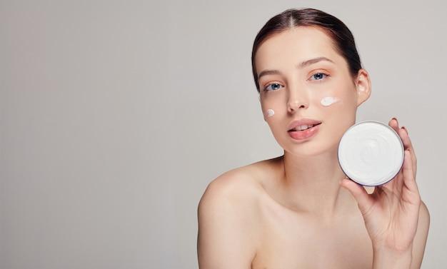 Hermosa mujer joven con la piel limpia y fresca. mujer que sostiene la crema en su mano izquierda en blanco. concepto de spa y cuidado.
