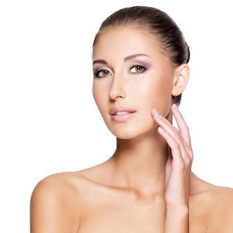 Hermosa mujer joven con piel limpia y fresca que toca su rostro con una mano, isolaten en blanco