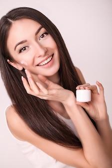 Hermosa mujer joven con la piel limpia y fresca toque la cara. tratamiento facial, cosmetología, belleza y spa.