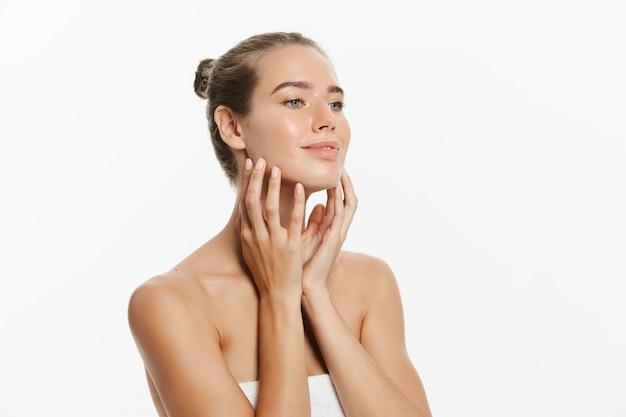 Hermosa mujer joven con la piel limpia fresca toque propio rostro. tratamiento facial.