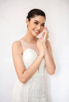 Hermosa mujer joven con piel limpia y fresca toque su propia cara tratamiento facial cosmetología belleza y spa