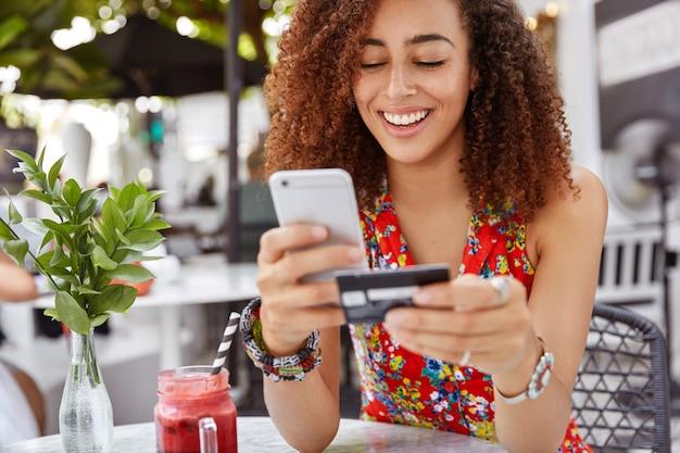 Hermosa mujer joven de piel oscura con expresión alegre, tiene teléfono inteligente y tarjeta de crédito, bancos en línea o hace compras mientras se sienta contra el interior del café.