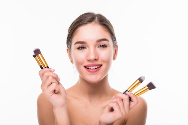 Hermosa mujer joven con pinceles de maquillaje cerca de su rostro aislado en la pared blanca