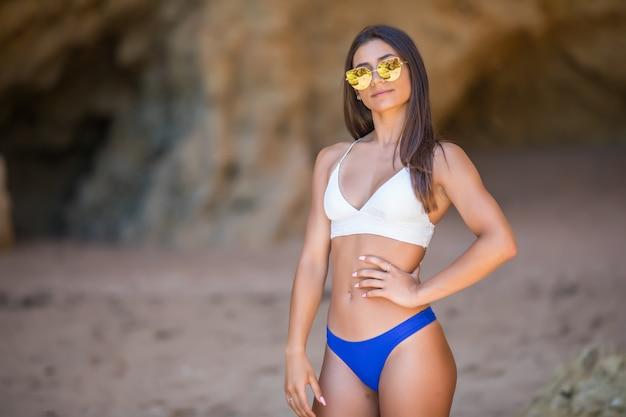 Hermosa mujer joven en la playa mirando a la cámara. feliz chica latina en bikini blanco sonriendo.