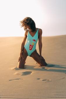 Hermosa mujer joven posando en la arena en un desierto de dunas