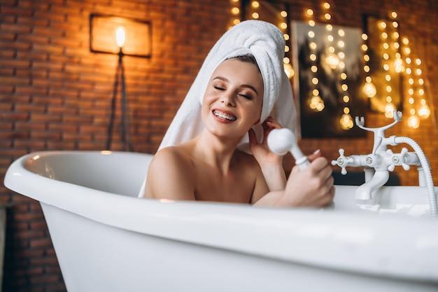 Una hermosa mujer joven posando. mujer acostada en un baño blanco con una toalla en la cabeza. una pared de ladrillo rojo con guirnaldas amarillas.
