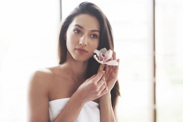 Hermosa mujer joven posando con orquídeas. tratamiento para el cuidado de la piel.
