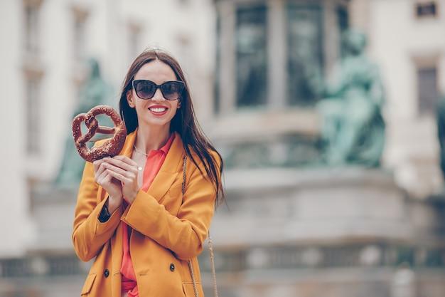 Hermosa mujer joven con pretzel y relajarse en el parque